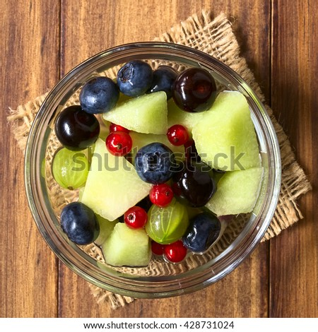 Fresh fruit salad made of cantaloupe melon, blueberry, redcurrant, gooseberry and sweet cherry in glass bowl, photographed overhead on dark wood with natural light - stock photo