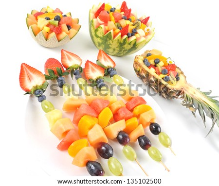 Fresh fruit salad of mango, strawberry, kiwi, grapes, strawberries blueberries banana in a bowl from watermelon honeydew and pineapple and fruit kebabs, brochette isolated on white - stock photo