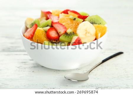 Fresh fruit salad on white wooden background - stock photo