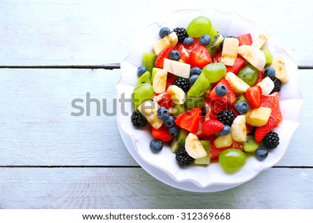 Fresh fruit salad on wooden table - stock photo