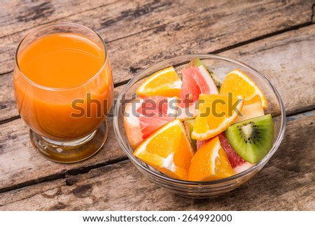 Fresh fruit salad with glass of apple and carrot juice on old wooden table. Eco food vitamins background - stock photo