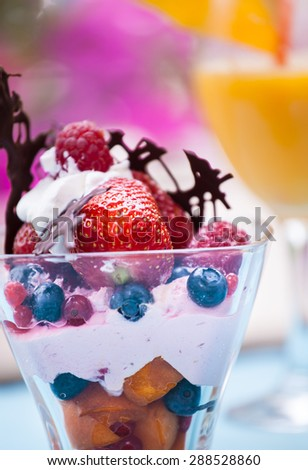 Fresh Fruit salad with ice cream in cup on colorful background - stock photo