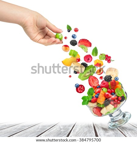 fresh fruit salad with ingredients in the air in a glass bowl on a wooden table - stock photo