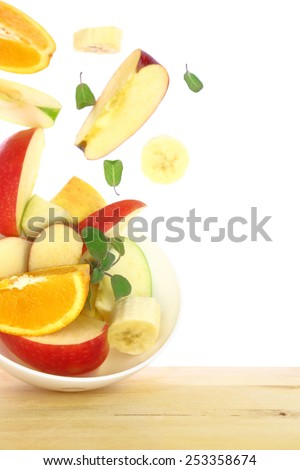 Fresh fruit salad with pieces flying out of a bowl isolated - stock photo