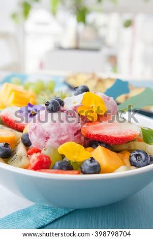 Fresh fruit salad with scoops of cherry ice cream - stock photo