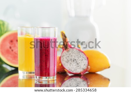 Fresh fruit smoothies on kitchen table. Blender is visible in background. Yellow mango juice and red pitaya juice on fruits background. Healthy eco food rich in vitamins. - stock photo