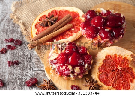 Fresh fruit tart with berries jam decorated with cranberry, cinnamon on wooden rustic background. Desert. Morning healthy breakfast and evening dinner. - stock photo