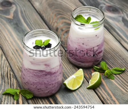 fresh fruit yogurt with blackberries and lime on a wooden background