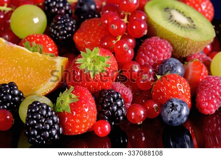 Fresh fruits and berries on a black background