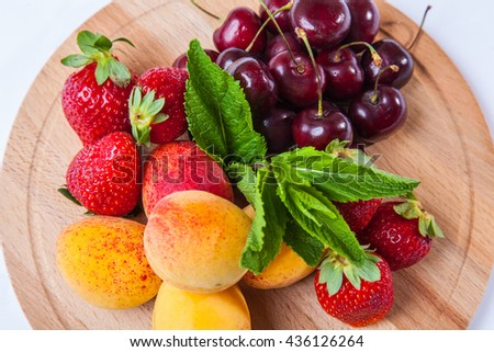 fresh fruits and berries on a wooden cutting board