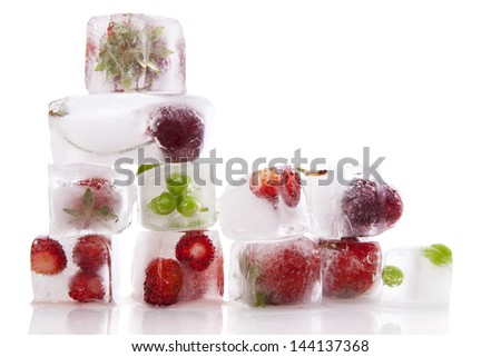 Fresh fruits and vegetable frozen in ice cubes isolated on white background. Fresh healthy summer eating. - stock photo