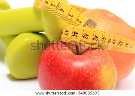 Fresh fruits, apple, grapefruit, tape measure and green dumbbells for using in fitness, concept for slimming, healthy nutrition and lifestyle
