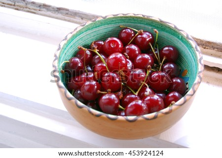 fresh fruits background with sour cherries in ceramic bowl