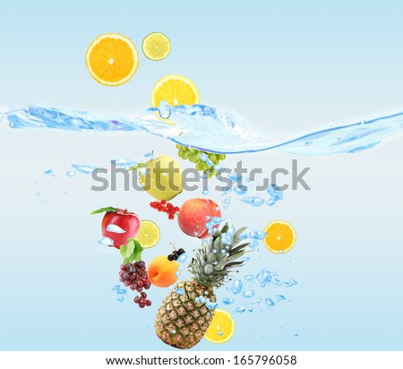Fresh fruits dropped into water - stock photo