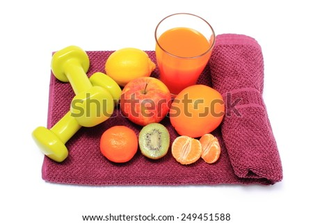 Fresh fruits, glass of juice and green dumbbells for using in fitness lying on purple towel, concept for slimming, healthy nutrition and strengthening immunity - stock photo
