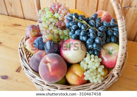 Fresh fruits in a basket: apple, peaches, pear, plums, nectarine, melon and grapes - stock photo