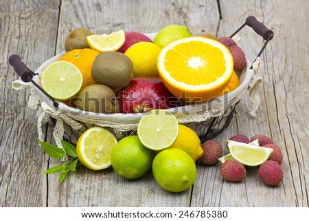 fresh fruits in a basket on wooden background - stock photo