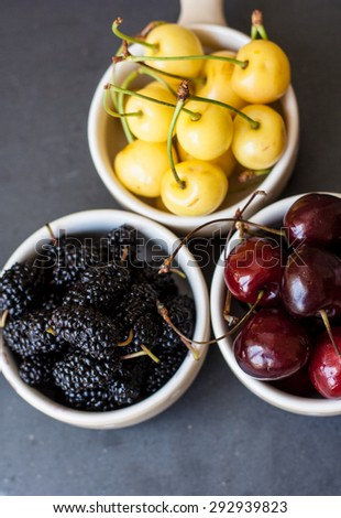 Fresh fruits in small bowls on a dark background