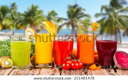 Fresh fruits juices on wood plant with tropical beach  - stock photo