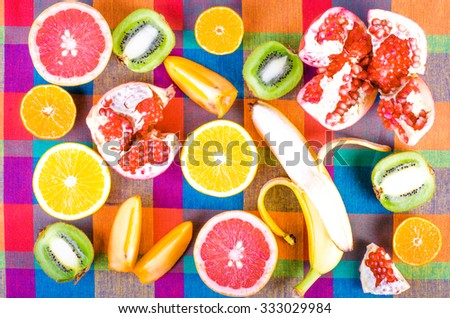 Fresh fruits on a colorful checkered kitchen towel. Raw and vegetarian eating background. Sliced orange, persimmon, kiwi, tangerine, banana, lemon, apple,  grapefruit, pomegranate, lime,  Top view - stock photo