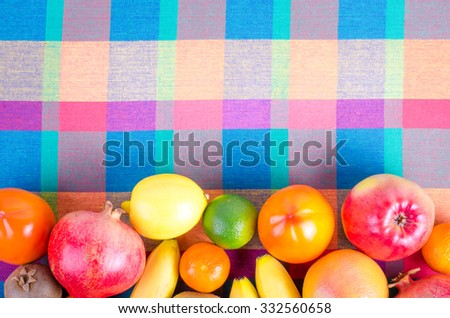 Fresh fruits on a colorful checkered kitchen towel. Summer background. Raw and vegetarian eating frame. Lemon, apple,  grapefruit, pomegranate, lime, persimmon, tangerine, orange, banana. Top view - stock photo