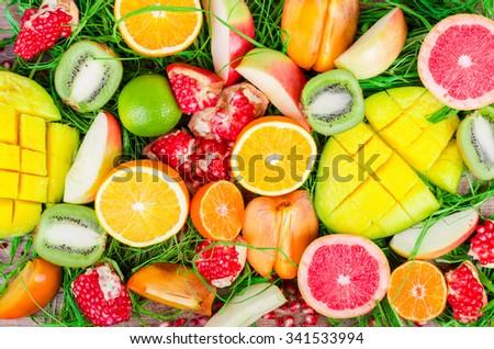 Fresh fruits on a wooden background. Raw and vegetarian eating frame. Sliced orange, persimmon, kiwi, tangerine, banana, lemon, apple,  grapefruit, pomegranate, lime, mango. Fruit set. - stock photo