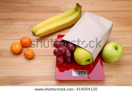 Fresh fruits on red digital kitchen scales over wooden background - stock photo