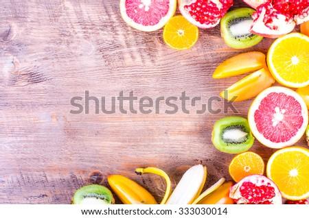 Fresh fruits on wooden background. Summer background. Raw and vegetarian eating frame. Sliced orange, persimmon, kiwi, tangerine, banana, lemon, apple,  grapefruit, pomegranate, lime,  Top view - stock photo