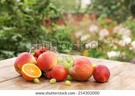 Fresh fruits, on wooden table, on green background - stock photo