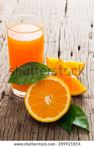 Fresh fruits Orange juice in glass on wood table - stock photo
