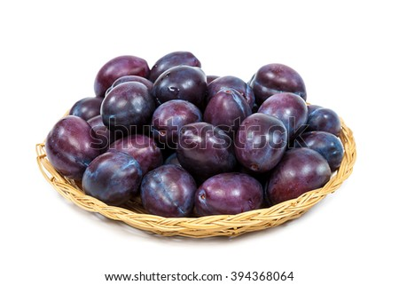 Fresh fruits plums in a wicker dish isolated on a white background. - stock photo