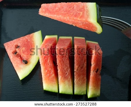 Fresh Fruits, Ripe and Sweet Refreshing Watermelon on Fork and Black Plate. - stock photo