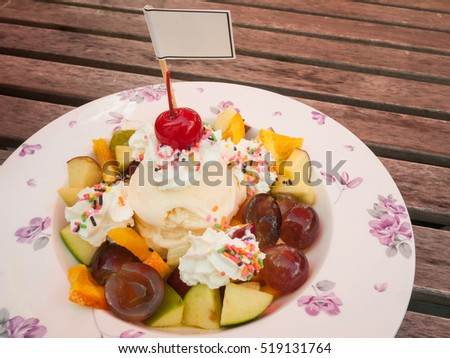 Fresh fruits salad with ice cream in plate and fruits on wooden background