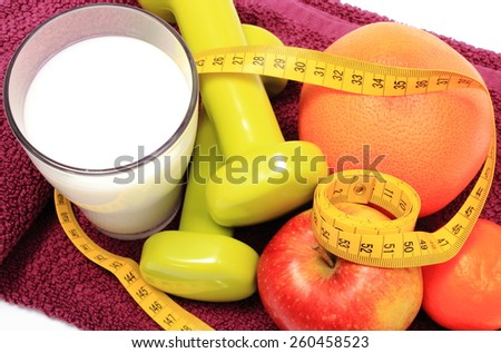 Fresh fruits, tape measure, glass of milk and green dumbbells for using in fitness lying on purple towel, concept for slimming, healthy nutrition and lifestyle