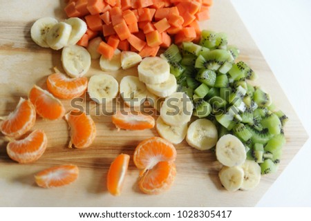 Fresh fruits which high vitamins had been chop in to small pieces on wooden board with white background. Healthy foods are ready for you.