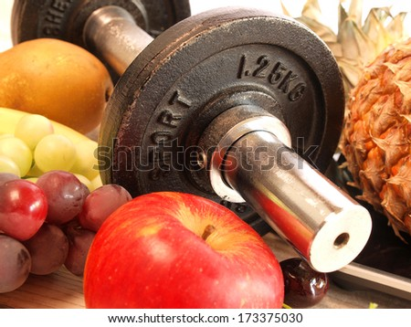 Fresh fruits with sports equipment - stock photo