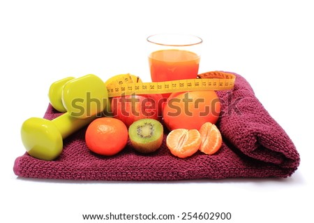 Fresh fruits with tape measure, glass of juice and green dumbbells for fitness lying on purple towel, concept for slimming, healthy nutrition and strengthening immunity - stock photo