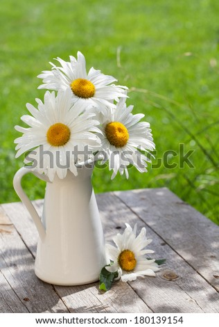 Fresh garden chamomile bouquet in vase on wooden table - stock photo
