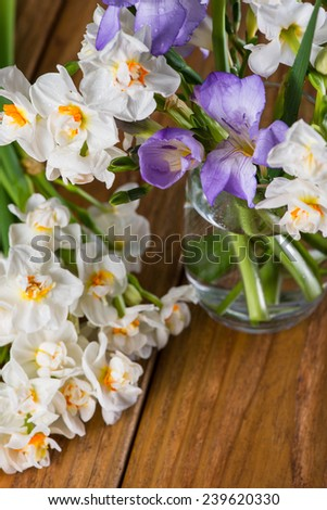 fresh garden flowers in glass on wooden table - stock photo