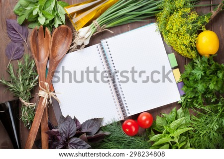Fresh garden herbs and notepad for your recipes on wooden table - stock photo