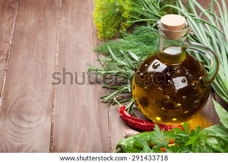 Fresh garden herbs and olive oil on wooden table. View with copy space - stock photo