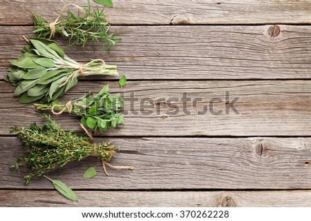 Fresh garden herbs on wooden table. Oregano, thyme, sage, rosemary. Top view with copy space - stock photo