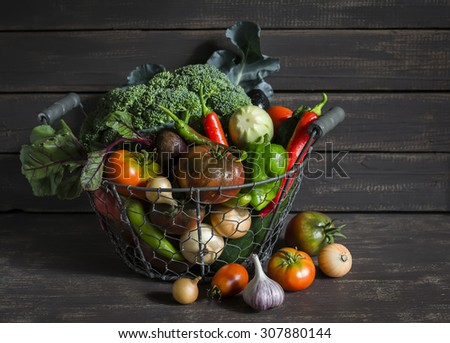 fresh garden vegetables - broccoli, zucchini, eggplant, peppers, beets, tomatoes, onions, garlic - vintage metal basket on a dark wooden background - stock photo