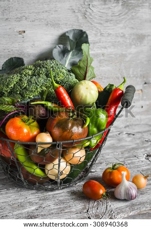 fresh garden vegetables - broccoli, zucchini, eggplant, peppers, beets, tomatoes, onions, garlic - vintage metal basket on a light wooden background - stock photo