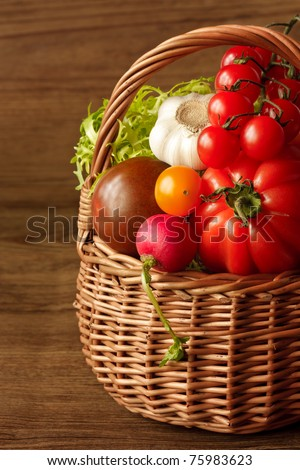 Fresh garden vegetables in a wicker basket on a wooden table.