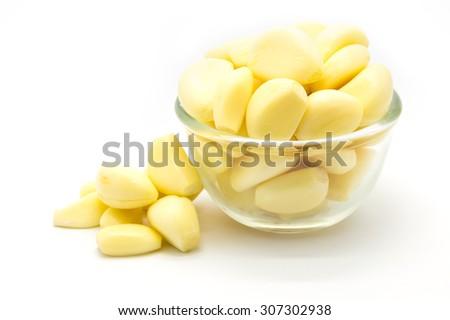 Fresh garlic in glass bowl on white  - stock photo