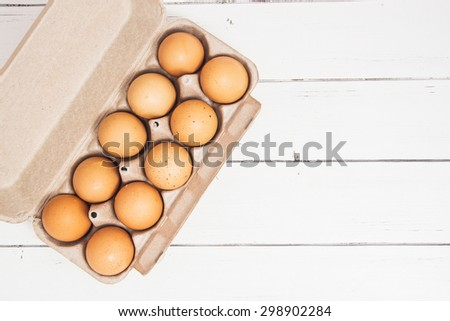 Fresh ginger eggs packed in a gray ecological paper container on a white wooden table background - stock photo