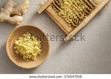 Fresh ginger granules in washboard and wooden plate,  fresh root ginger on the linen - stock photo