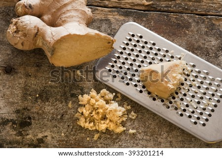Fresh ginger root, shavings and stainless steel grater over old worn out wooden table - stock photo