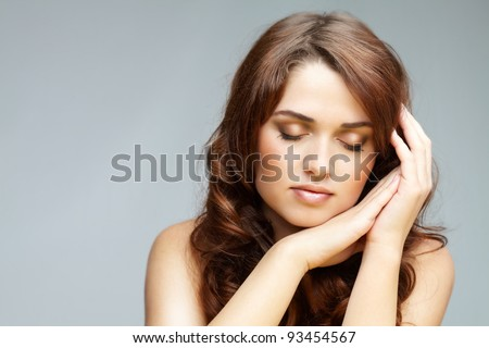 Fresh girl with closed eyes touching her cheek in isolation - stock photo